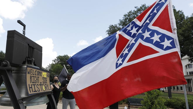 "A Mississippi state flag waves adjacent to a flag change supporter's sign that welcomes the state to ""the right side of history,"" outside the Capitol in Jackson, Miss., Sunday, June 28, 2020, while lawmakers are expected to consider state flag change legislation. Mississippi Governor Tate Reeves has already said he would sign whatever flag bill the Legislature decides on."