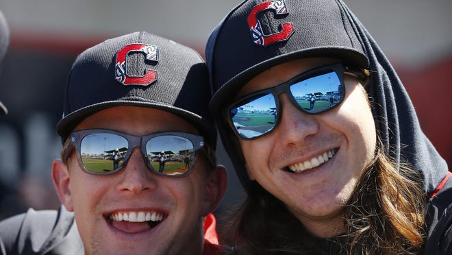 Cleveland Indians starting pitchers Zach Plesac, left, and Mike Clevinger, right, smile for a photo as they stand in the dugout prior to a spring training baseball game against the Chicago Cubs, Saturday, March 7, 2020, in Goodyear, Ariz.