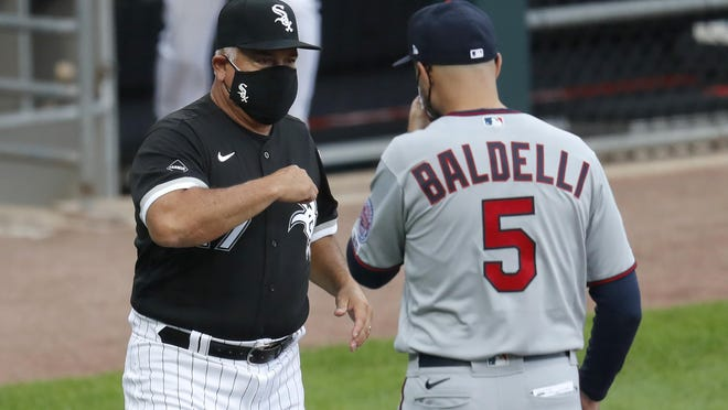 Chicago White Sox manager Ricky Renteria, left, bumps elbows with Minnesota Twins' manager Rocco Baldelli, before the White Sox's home opener baseball game Friday, July 24, 2020, in Chicago.