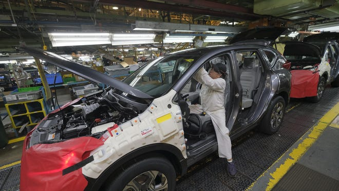 A worker installs interior components into a Honda CR-V on the assembly line at the Honda manufacturing plant in Marysville in 2018.