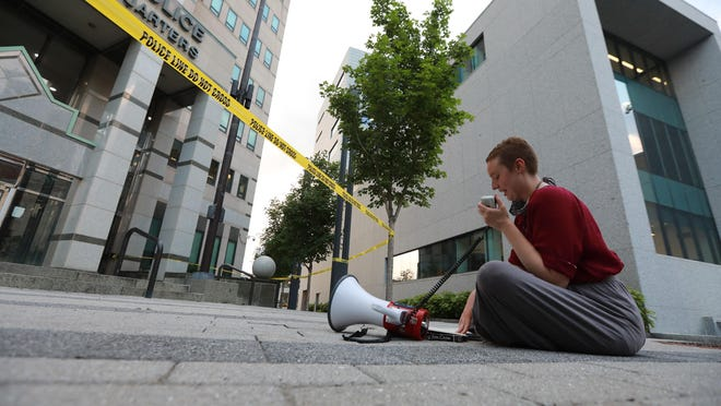 Samantha Grimsley uses a bullhorn outside Columbus police headquarters Downtown as she reads aloud from books about racism in the criminal justice system and alternatives for policing.