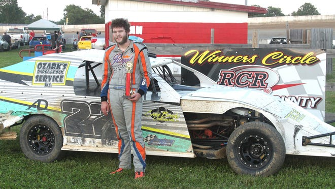 Cole Campbell of Mexico stands in front of his vehicle as he holds onto the first place trophy he won Sunday in winning the B-Modified feature at Randolph County Raceway in Moberly.