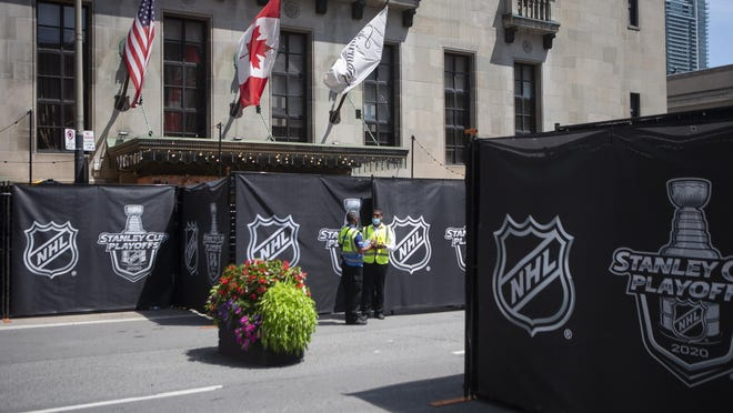 """Security guards stand by Sunday at a section of the street outside Toronto's Royal York hotel, which is closed off as NHL teams arrive at the """"bubble"""" ahead of the return of the league's season following a disruption because of the COVID-19 pandemic."""