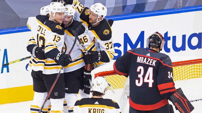 The Bruins' Charlie Coyle (13) celebrates his goal against Hurricanes goaltender Petr Mrazek with teammates during the second period on Saturday.