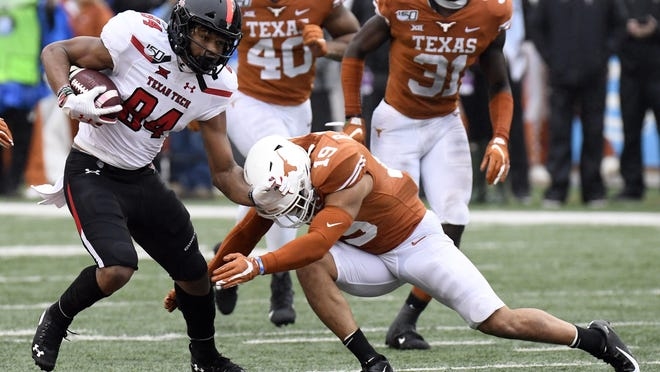 Texas Tech wide receiver Erik Ezukanma (84) tries to shed a tackle attempt by Texas defensive back Brandon Jones (19) during last year's game in Austin. Ezukanma caught seven passes for 135 yards and a touchdown, but the Longhorns won 49-24.