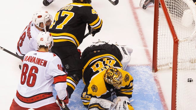 Boston Bruins goaltender Tuukka Rask (40) watches the puck cross the line on what would be ruled no goal due to goalie interference as Carolina Hurricanes' Teuvo Teravainen (86), Hurricanes' Jordan Martinook (48) and Bruins' Torey Krug (47) look on during third-period NHL hockey first-round Stanley Cup playoff action in Toronto, Thursday, Aug. 13, 2020.