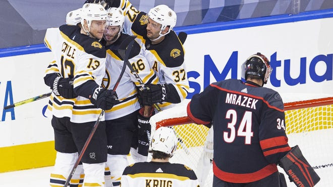 Boston Bruins' Charlie Coyle (left) celebrates his goal against Carolina Hurricanes' goaltender Petr Mrazek with teammates during the second period of a NHL Eastern Conference Stanley Cup playoff game in Toronto on Saturday.