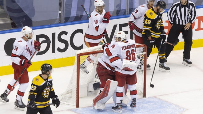 Carolina's Teuvo Teravainen (86) hugs goaltender James Reimer (47) as the buzzer sounds as they defeat the Boston Bruins in a Stanley Cup playoff game in Toronto on Thursday.