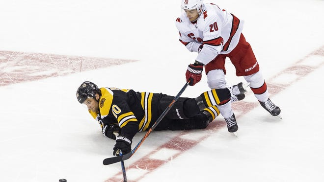 Boston Bruins' Anders Bjork (10) falls in front of Carolina Hurricanes' Sebastian Aho (20) during the third period of an NHL Eastern Conference Stanley Cup hockey playoff game in Toronto, Thursday, Aug. 13, 2020.