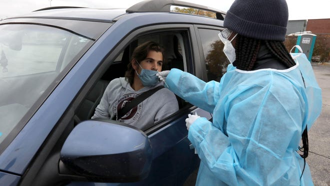 Ross Ewing gets a drive-thru COVID-19 test from phlebotomist Sydnie Booker at a testing site in the parking lot of the Foreman Mills Shopping Center in Chicago on Oct. 19, 2020.