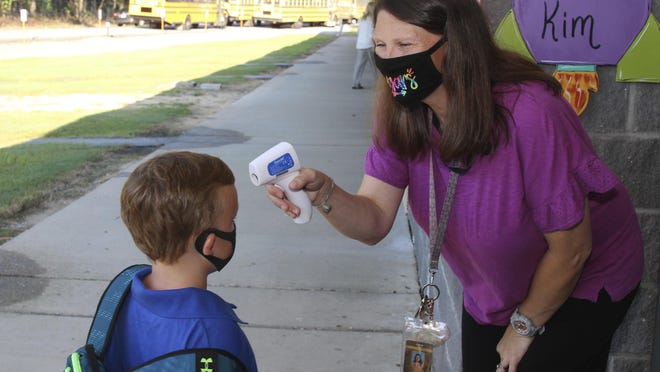 Teaching assistant Crystal May talks to kindergarten student Lewis Henry Thompson, 5, as she takes his temperature at Newton County Elementary School in Decatur, Miss., Aug. 3. Schools and daycare centers across the country have had to navigate changing guidelines to protect students from the pandemic.