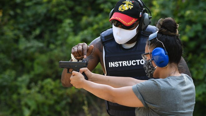 NRA instructor Stephen Alexander of Okemos teaches Erica Lynn of Lansing site placement and target acquisition Saturday, July 26, 2020, during a handgun training session at the Chief Okemos Sportsman's Club in Dimondale.  Alexander served nine years in the U.S. Marine Corps and is vice-president of the Malcolm Little Gun Club.