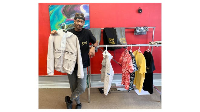 Zay Turnage of Monroe holds up a piece of apparel he is debuting for his business, A Chosen Few Threads. He recently opened a headquarters in downtown Monroe.