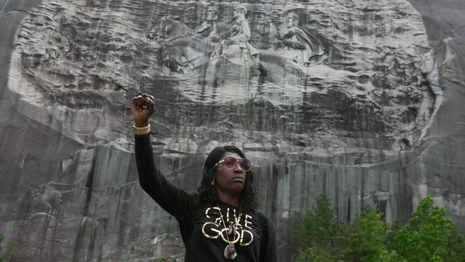 STONE MOUNTAIN, GA - JUNE 16: Lahahuia Hanks holds up a fist in front of the Confederate carving at Stone Mountain Park during a Black Lives Matter protest on June 16, 2020 in Stone Mountain, Georgia. The march is to protest confederate monuments and recent police shootings.  Stone Mountain Park features a Confederate memorial carving depicting Stonewall Jackson, Robert E. Lee, and Jefferson Davis, President of the confederate states.