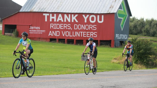 From left: Elaine Natsis, Rudy Holliday and Scott Sommers ride past a barn painted to support Pelotonia during a recent training ride.