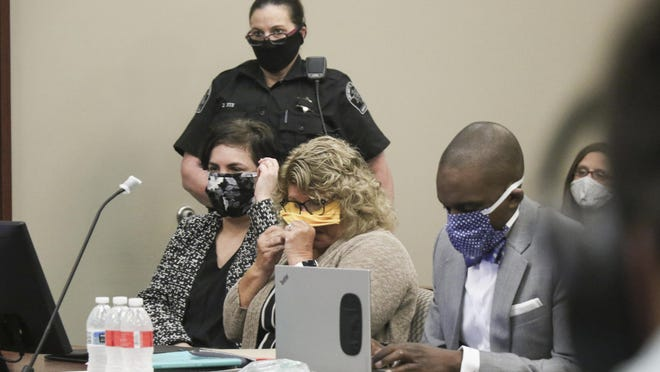 Flanked by her attorneys Mary Chartier, left, and Takura Nyamfukudza, right,  former Michigan State gymnastics coach Kathie Klages reacts during testimony in Judge Joyce Draganchuk's courtroom Tuesday, during Klages' sentencing hearing in Lansing. Klages was found guilty of two counts of lying to police related to an interview about her knowledge of Larry Nassar's abuse in 1997. Draganchuk sentenced her to 90 days in jail with credit for one day served.