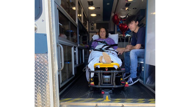 Monroe Police Department Cpl. Renae Peterson is joined by her son in the ambulance during her ride from a Toledo hospital to a rehabilitation center in Ann Arbor on Tuesday. Nearly 50 first responders filled the on- and off-ramps of northbound US-23 in Dundee to show support for Peterson.