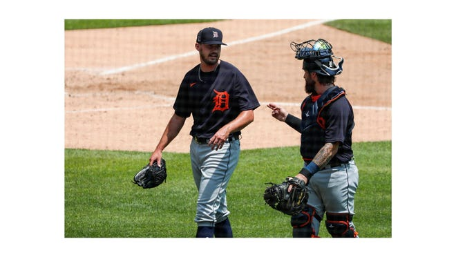 Gibraltar Carlson graduate John Schreiber (left) talks to Detroit Tigers catcher Eric Haase during an intrasquad game during summer camp at Comerica Park last month.