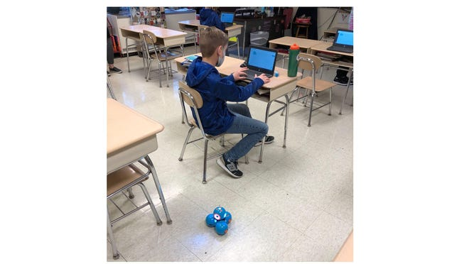 Fifth graders in Jessica Thompson's seminar science class at Ida Elementary School works on code with his robot at his feet.