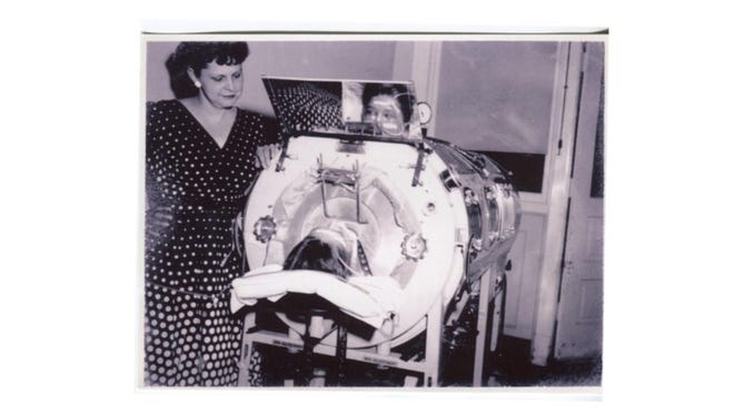 Richard Holcomb, 12, lies in an iron lung in 1954. He can see his mother in the mirror over his head. This was his last photo.