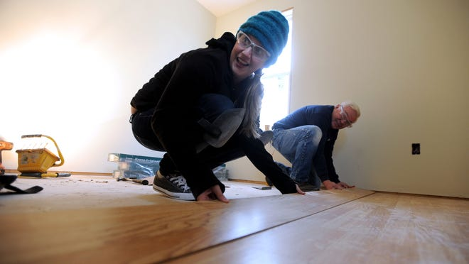 Beth Walton of the Asheville Citizen-Times and Habitat for Humanity of Asheville volunteer Ralph Johnson work to install flooring at a home under construction off Johnston Boulevard.