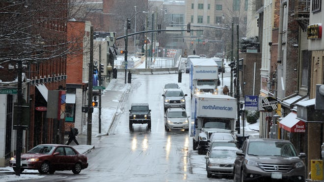 Pedestrians and traffic move along College Street in Asheville. Rain could turn to freezing rain, snow and sleet Thursday.