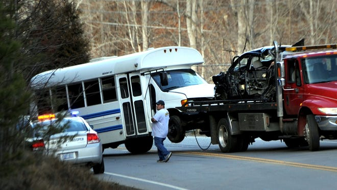 A white bus is towed behind a wrecker carrying a gray Toyota sedan following a fatal accident  on Barnardsville Highway in 2015.