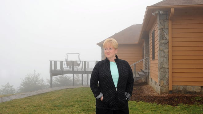 """Brenda Thompson, broker and president of Special """"Finds"""" real estate group based in Asheville, stands for a picture at a home off Flicker Trail near Weaverville."""
