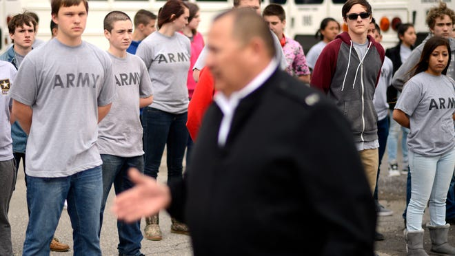 Chief Tony Gutierrez, a U.S. Army veteran and teacher at Erwin High School, center, speaks with students in the school's JROTC program Tuesday afternoon, before the start of drills in the school's parking lot.