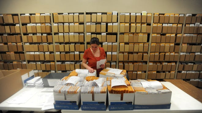 Buncombe County courts employee Rachel Long looks through some of the thousands of files kept in the Buncombe County courthouse. Some people who work in the state courts system say a lack of funding means it has been too slow to convert to an electronic document system.