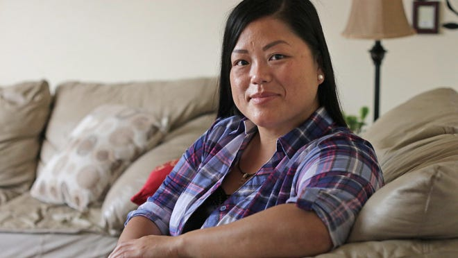 Mai Lee poses in her home Friday in Sheboygan.