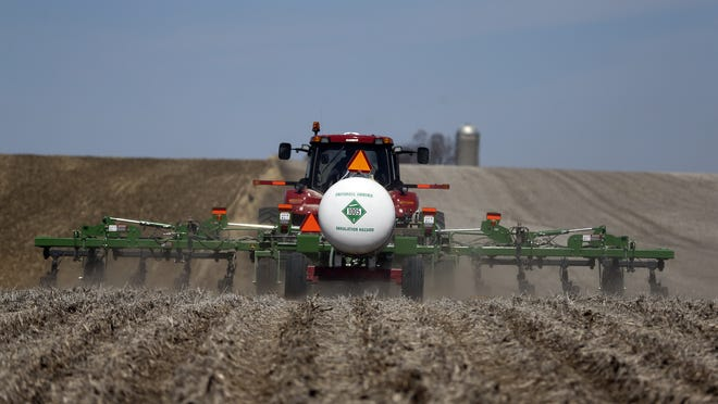 Craig Boot pulls a tank of anhydrous ammonia behind his tractor April 9 before injecting the chemical into the soil in preparation for spring planting in a corn field near the Marion and Mahaska County line outside Pella.