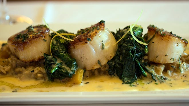 The coquille Saint-Jacque at Bistro Le Relais is seared scallops with butternut squash mushroom risotto and orange sage beurre blanc.