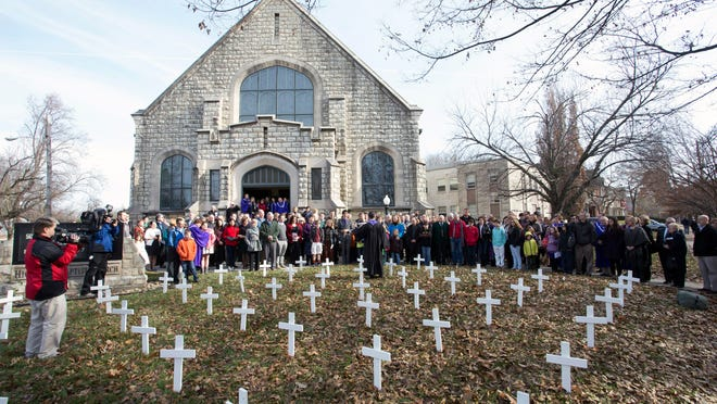 Members of Highland Baptist Church gathered after a recent Sunday service to honor Louisville's 56 murder victims of 2014. A small white cross was erected for each victim on the front lawn of the 100-year-old church at the corner of Grinstead Drive and Cherokee Parkway.