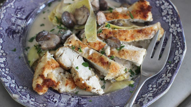 This Jan. 19, 2015 photo shows chicken with tangy artichoke and mushroom sauce in Concord, N.H. (AP Photo/MatthewMead)
