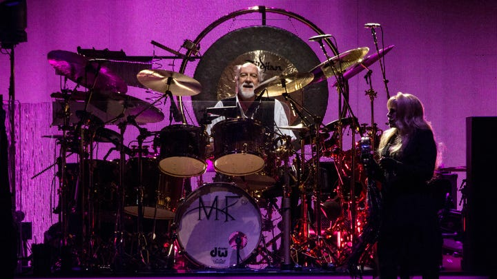 Mick Fleetwood peers out from behind his drums during the Fleetwood Mac concert at the KFC YUM! Center on Tuesday night. 2/17/15