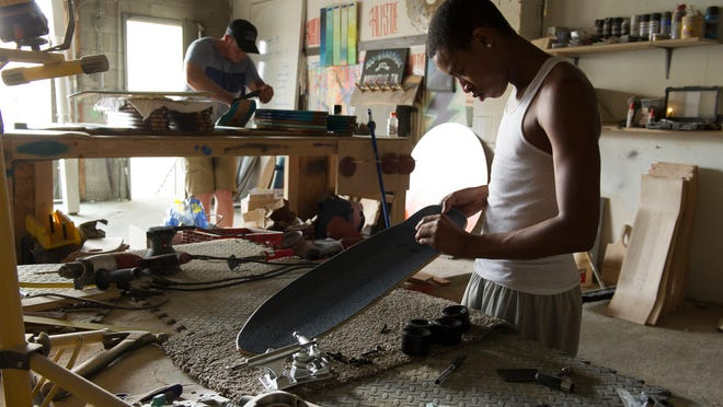Salemtown Board Co owner Will Anderson assembles skateboards with Kendrius Smith Thursday, May 29, 2014 in Nashville, Tenn. Will believes that social responsibility is part of running a business, and specifically hired Kendrius and another teen from Salemtown to provide jobs where they are scarce. He plans to hire more area teens as the business grows.