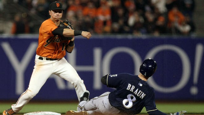 Aug 29, 2014; San Francisco, CA, USA; San Francisco Giants second baseman Joe Panik (12) makes the double play during the eighth inning against the Milwaukee Brewers at AT&T Park. Mandatory Credit: Lance Iversen-USA TODAY Sports.