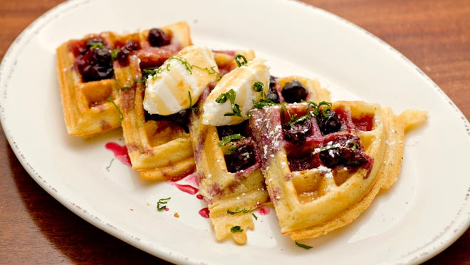 A feathery Belgian waffle is cut into four wedges to hold the toppings for Chestnut's lemon ricotta waffles.