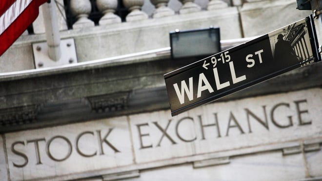 This July 16, 2013, file photo shows a Wall Street street sign outside the New York Stock Exchange in New York.