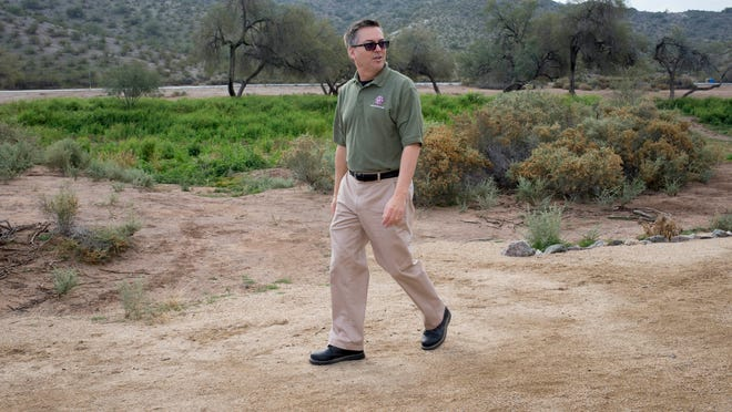 Don Harris, the supervisor of Estrella Mountain Regional Park, walks what was supposed to be a Centennial Trail. The plan initially included historical markers, exhibits, kiosks and benches.