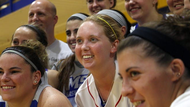 Lauren Hill, center,  poses for a photo with her teammates after practicing with the NCAA college basketball team at Mount St. Joseph University in Cincinnati on Thursday, Oct. 23, 2014. Hill had made her choice. She would play basketball at the Division III school in the suburbs. Soon afterward, she started feeling bad and got tests that found an inoperable mass in her brain. (AP Photo/Tom Uhlman)