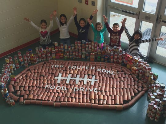 """Students at Three Bridges School in Readington are tackling hunger. The Third Grade Student Voice at Three Bridges School recently conducted a canned soup drive for the """"Souper Bowl."""" The students collected 700 cans of soup which were donated to the Flemington Food Pantry. In the above photo (from left) Megan Keller, Amelia Cassidy, Maddie Yip, Emilia Barca, Joey Caruso and Sydney Artache proudly display the giant football created with the donated items."""