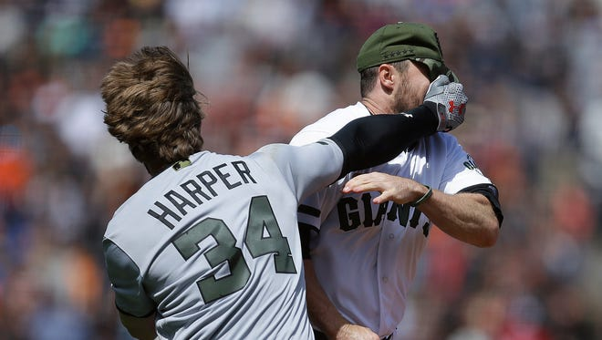 Washington Nationals' Bryce Harper (34) hits San Francisco Giants' Hunter Strickland in the face after being hit with a pitch in the eighth inning of a baseball game Monday, May 29, 2017, in San Francisco.