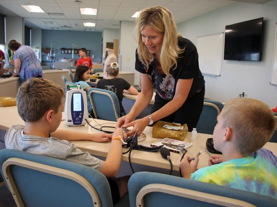 "Brianna Neuser, director of nursing at Silver Lake College of the Holy Family, helps two Manitowoc Public School District students take their blood pressure and blood oxygen level readings. The boys were among Manitowoc Public School District summer school students who visited the college to learn about nursing through the ""A Day in the Life"" program, taught by Gina Blaser. The students listened to their heart and lung sounds with stethoscopes, learned how to give injections using fake human skin pads and met Frankie, the college's high-fidelity medical manikin."