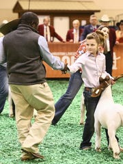 A judge congratulates Cyndee Jo Hanslik after she won reserve grand champion goat at the Houston Livestock Show and Rodeo.