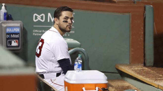 Boston Red Sox's Michael Chavis sits alone in the dugout after striking out for the fifth time during the ninth inning of their loss to the Philadelphia Phillies in a baseball game Tuesday, Aug. 18, 2020, at Fenway Park in Boston. (AP Photo/Winslow Townson) ORG XMIT: BXF10