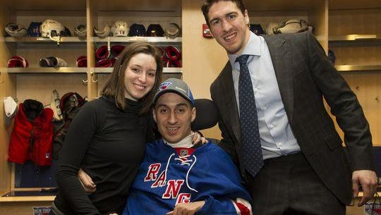 "Former Pelham hockey player Gino Mangiafridda, center, draws inspiration in his struggle to walk again from girlfriend Megan Seccante and Rangers captain Ryan McDonagh. Seccante says McDonagh ""doesn't do his one deed and then back off."""
