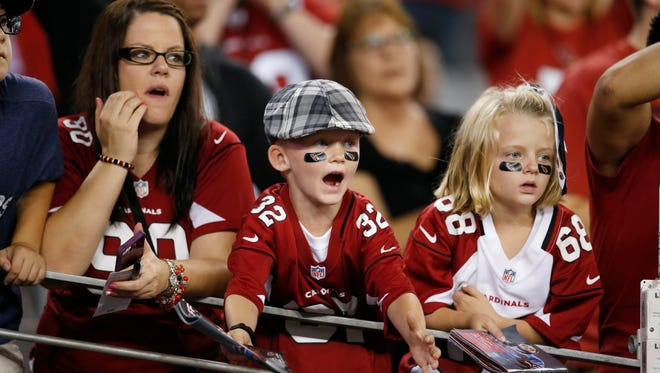 Cardinals fans look for autographs before the game against the San Diego Chargers at University of Phoenix Stadium in Glendale on Sept. 8, 2014.