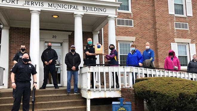 Members of the Port Jervis Rotary Club deliver protective masks to the Port Jervis Police Department. At center are Police Chief William Worden and Rotary President Angela Lee.